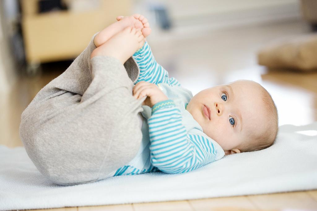 Малыш лежит на спине, не переворачивается, ножки согнуты, прижаты к туловищу