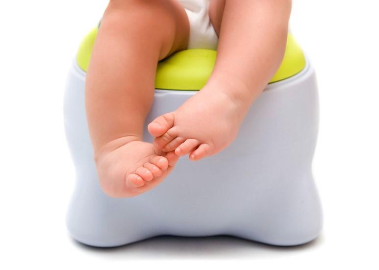 Ножки малыша, который сидит на горшке