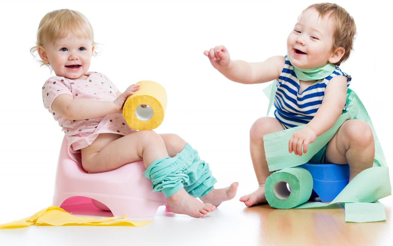 Мальчик и девочка сидят на горшках