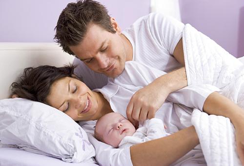 Младенец спит со счастливыми родителями