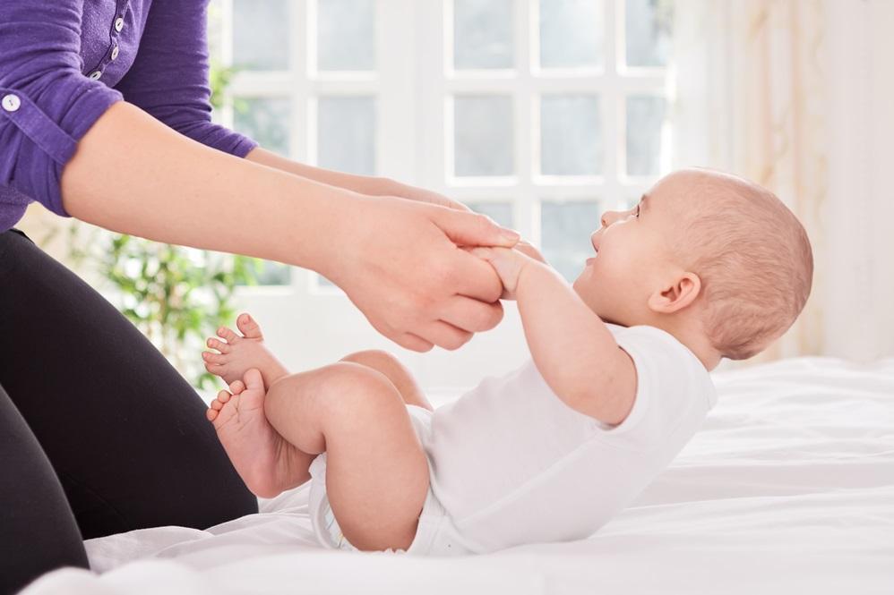 Ребенок держит голову, когда мама его поднимает в положение «сидя»