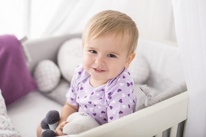 Малыш сидит в кроватке, улыбается и обнимает игрушку