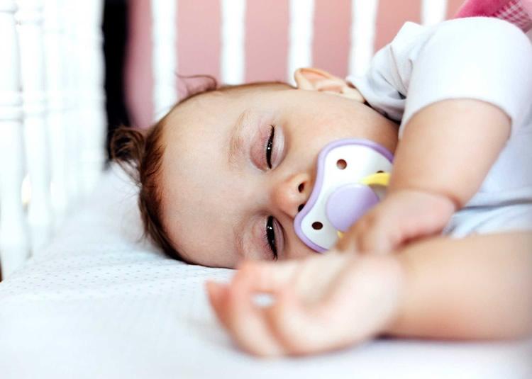 Ребенок спит в кроватке, у него соска во рту