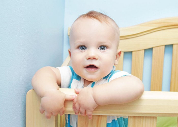 Ребенок стоит в кроватке и улыбается