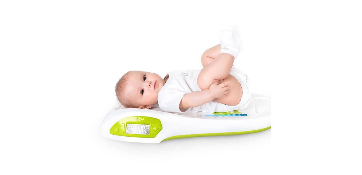 Маленький ребенок лежит на весах