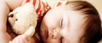 Ребенок спит в кроватке с игрушкой в руках