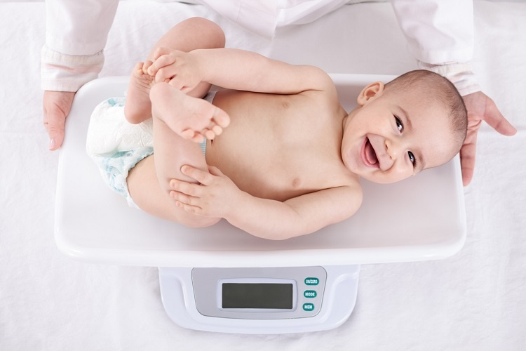Ребенок лежит на электронных весах и улыбается
