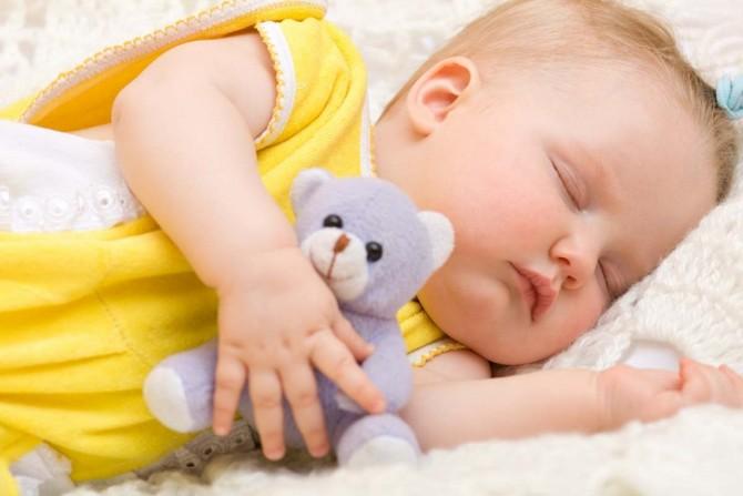 Ребенок спит и обнимает игрушку