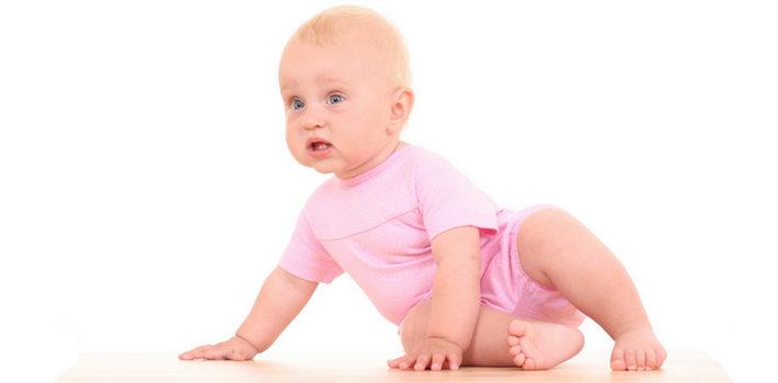 Ребенок в розовом костюме ползает по полу