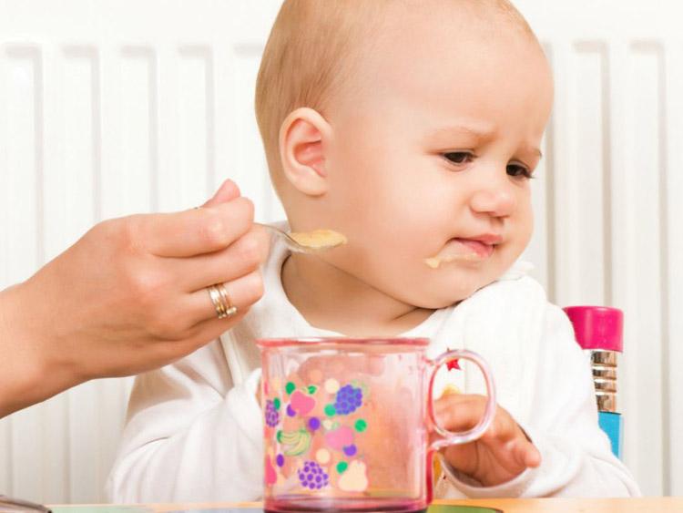 Ребенок сидит в стульчике для кормления и не хочет есть из ложки