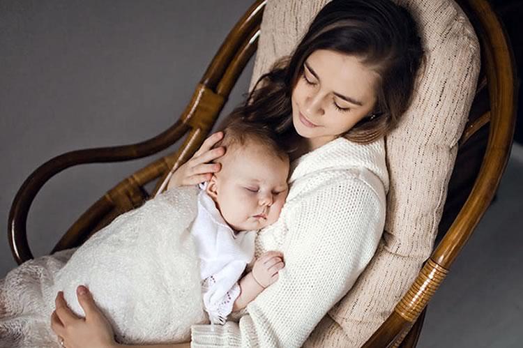 Ребенок спит на руках у мамы в кресле-качалке