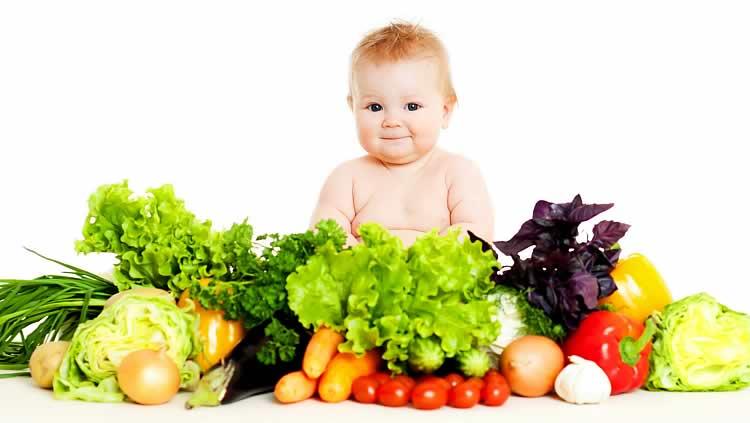 Годовалый малыш сидит рядом с большой горой овощей и зелени