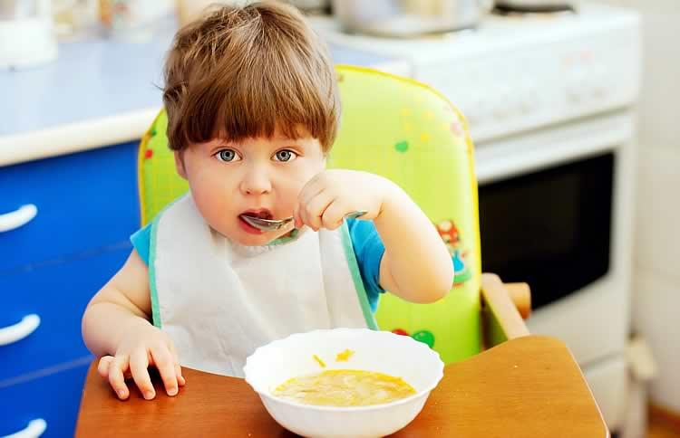 Годовалый ребенок сидит и ест суп ложкой