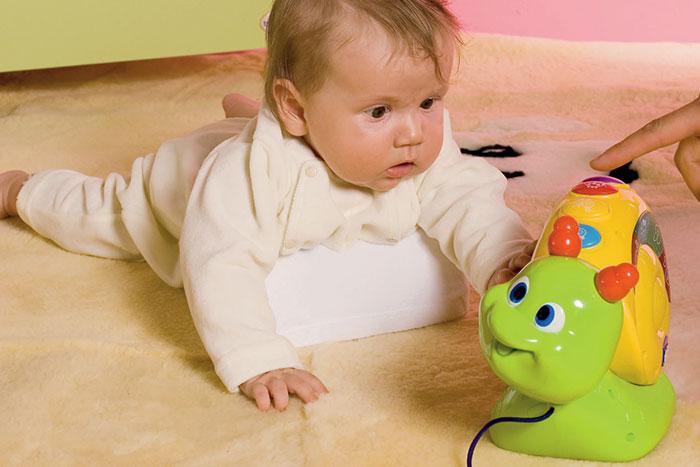 Ребенок ползет по полу к игрушке