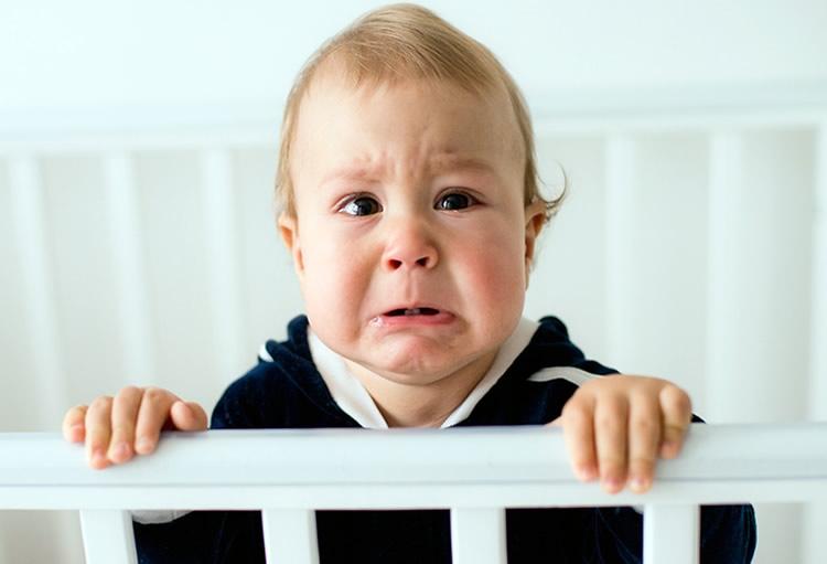 Ребенок стоит в кроватке и очень плачет