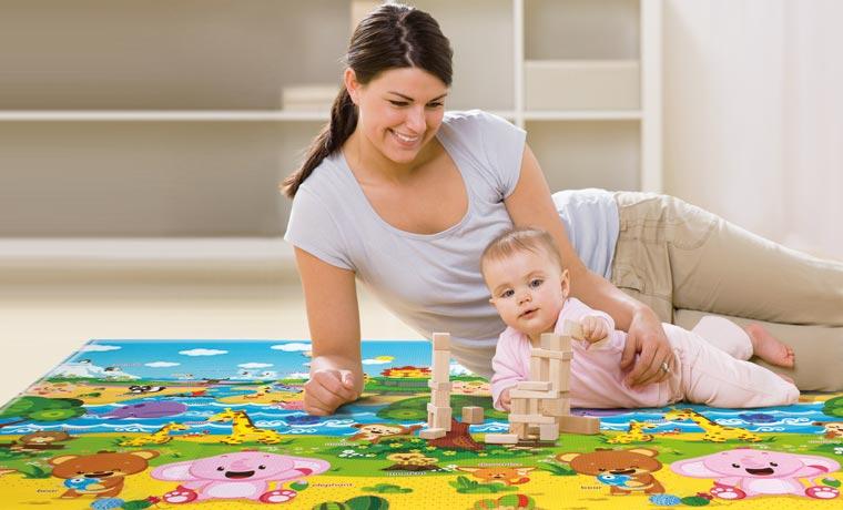 Ребенок ползает по коврику на природе