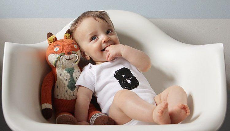 Ребенок сидит в кресле рядом с мягкой игрушкой
