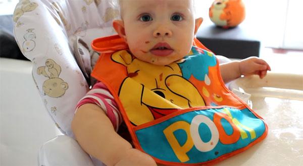 Здоровый 11-месячный малыш делает попытки самостоятельно держать ложку во время еды