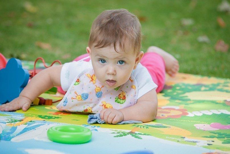 Ребенок 9 месяцев лежит на коврике на животике и играется игрушками