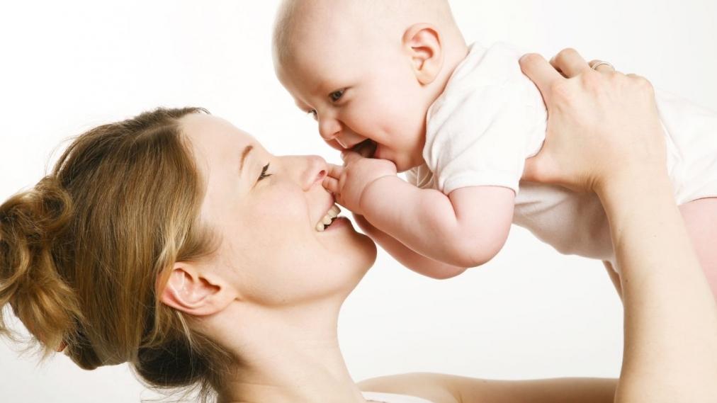 Ребенок на руках у мамы веселый