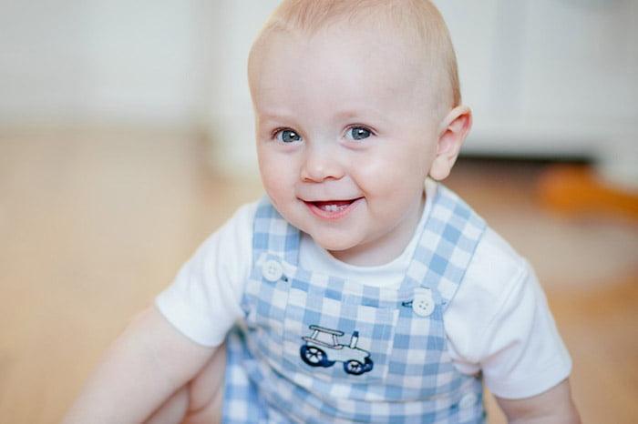 Ребенок в белой футболке и голубом полосатом комбинезоне сидит на полу