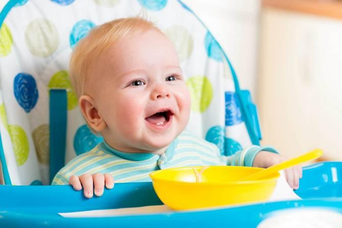 Ребенок сидит в детском стульчике для кормления и кушает