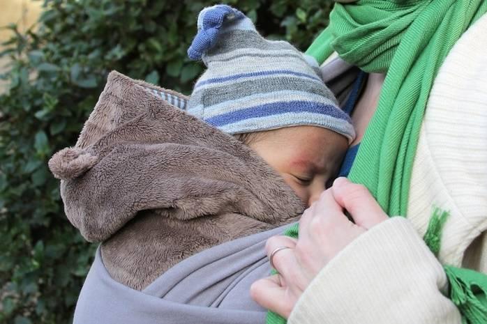 Ребенок на руках у мамы в сером костюмчике и шапочке на прогулке