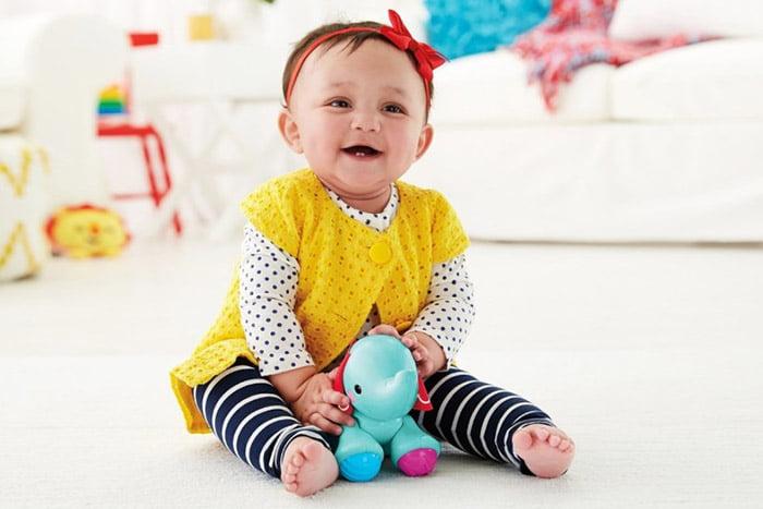 Ребенок девочка в 9 месяцев сидит и играет игрушками на полу