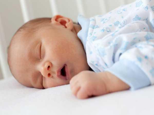 Маленький ребенок спит на животе