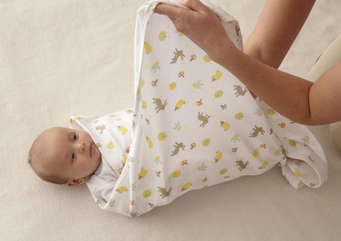 Ребенка заматывают в пеленку