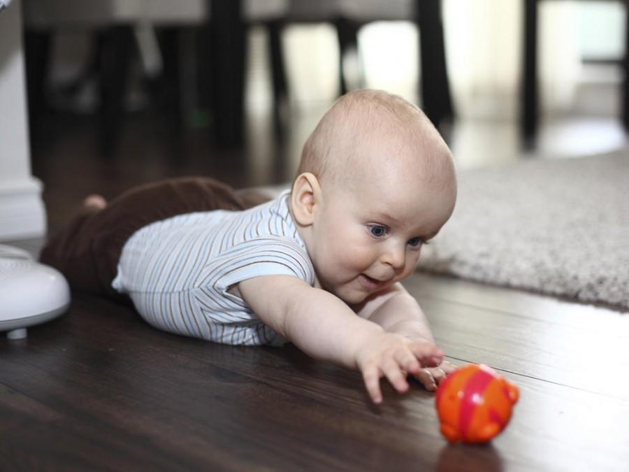 Малыш пробует дотягиваться до игрушек