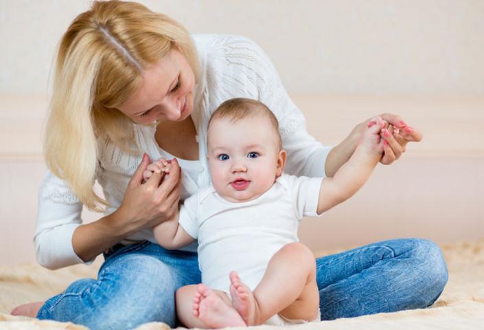 Ребенок учится сидеть с маминой поддержкой