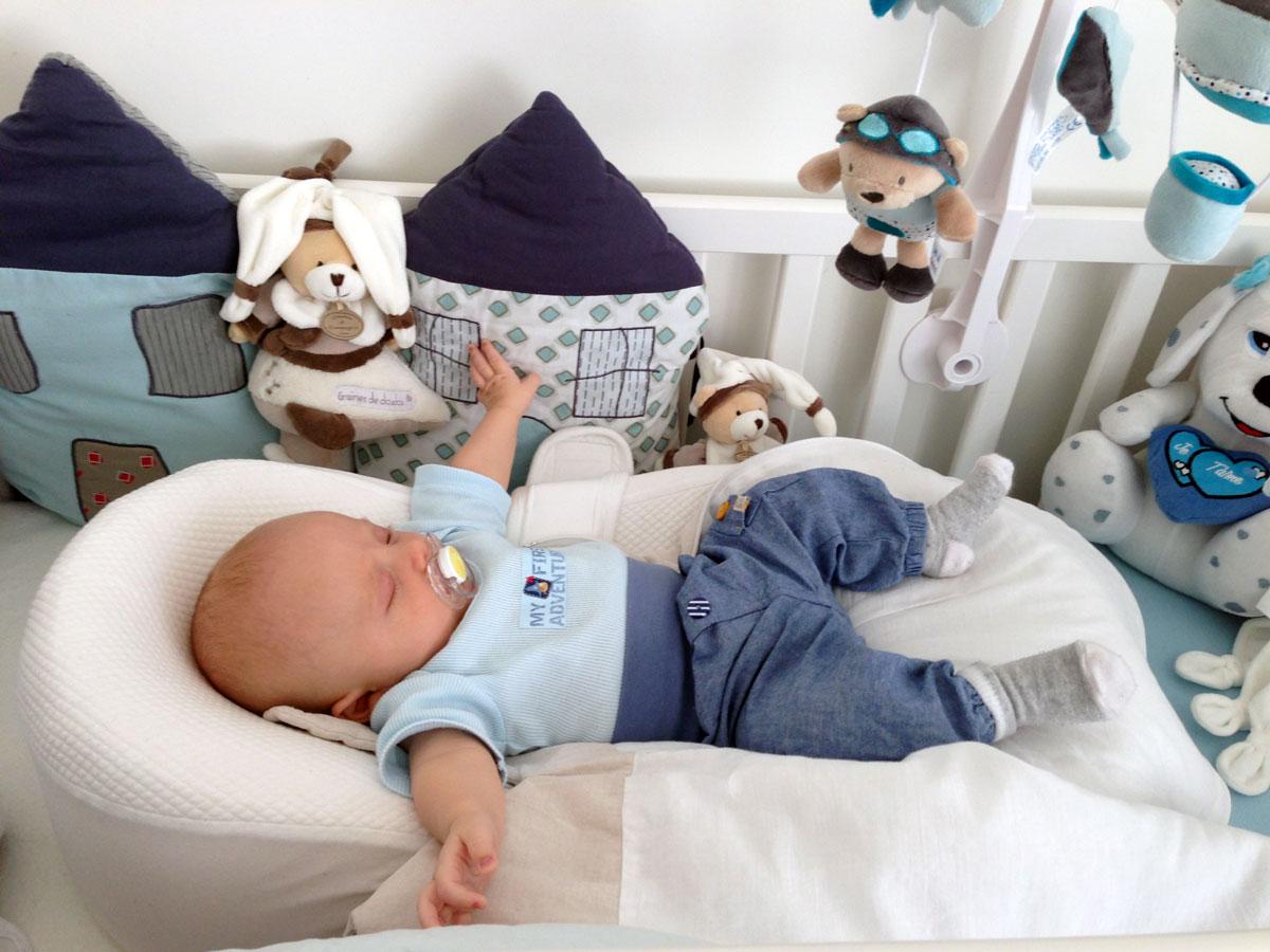 Детская кроватка и малыш в коконе