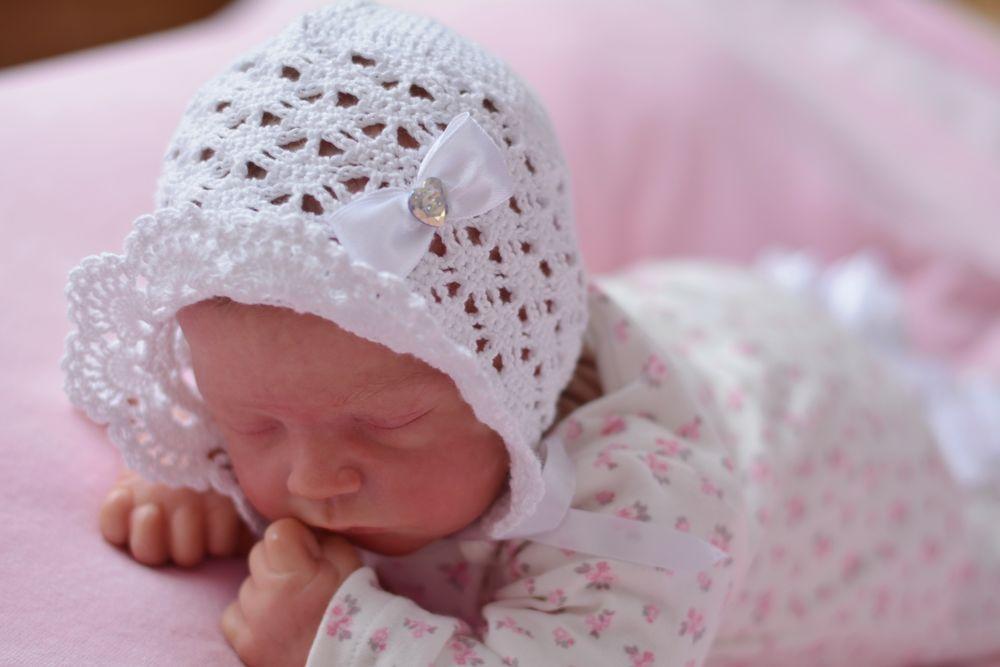 Новорожденная девочка в чепчике