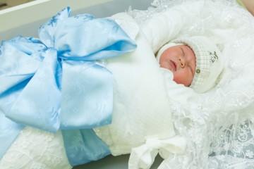 У новорожденного поддет чепец под теплую шапку