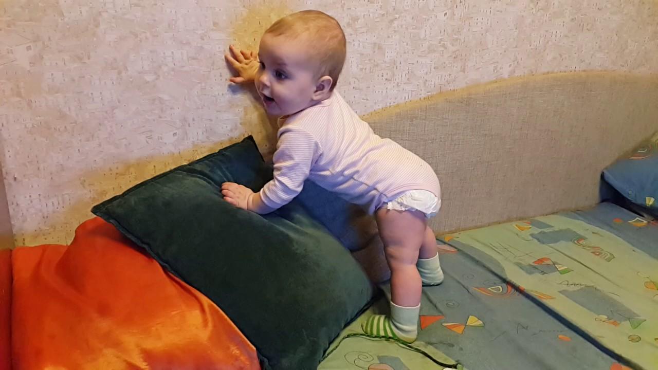 Малыш встает, держась за опору