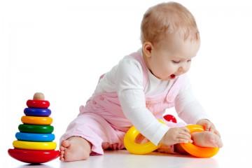 Годовалый малыш играет пирамидкой