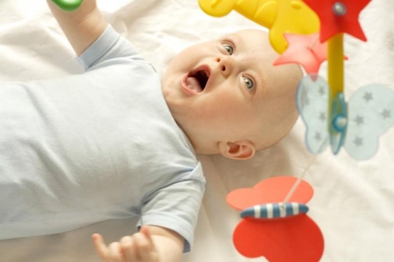 Пятимесячный ребенок играет с мобилем