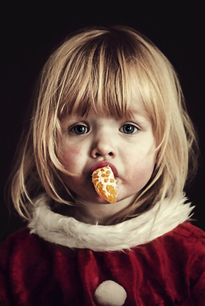 Девочка ест мандарин