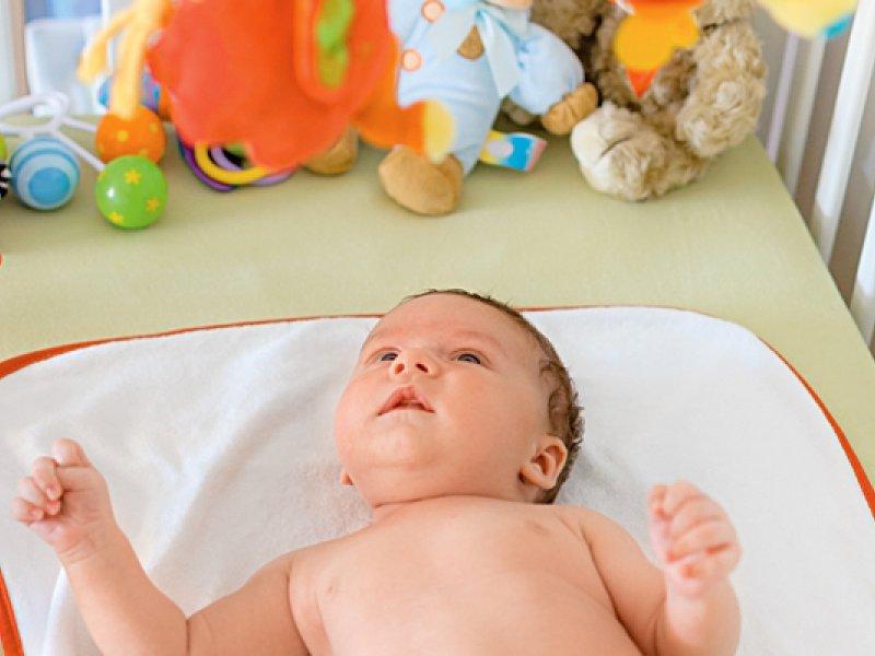 Малыш в кроватке с игрушками