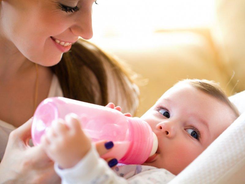 Младенец пьет из бутылочки смесь