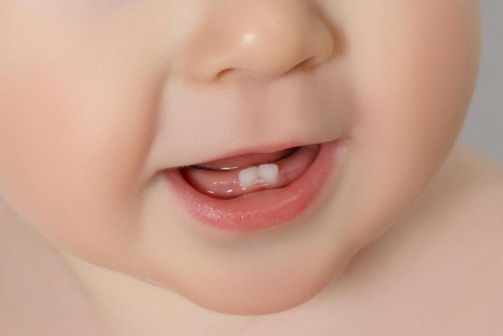 Как появляются первые зубы у младенца: во сколько месяцев начинают расти, симптомы