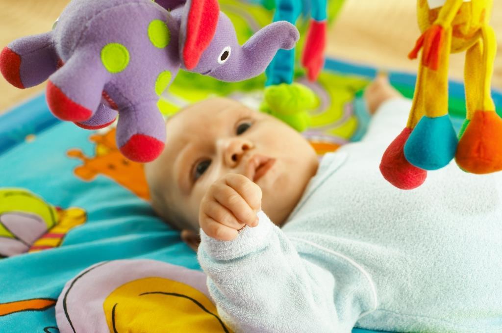 Новорожденный изучает игрушку