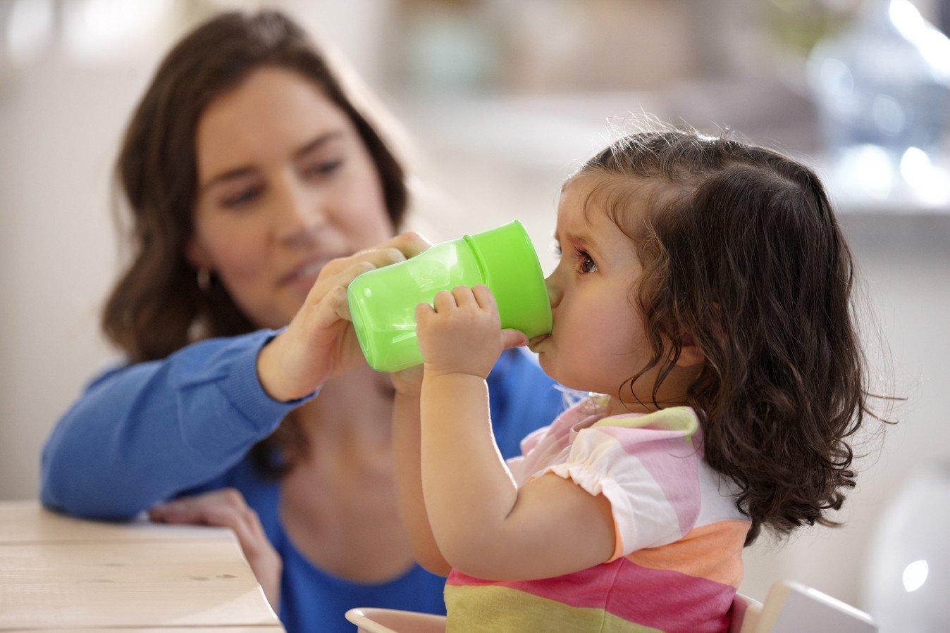 Мама учит дочку пить из чашки