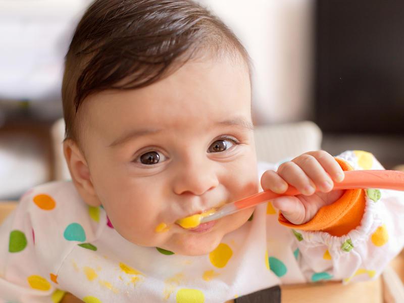 Младенец ест ложкой