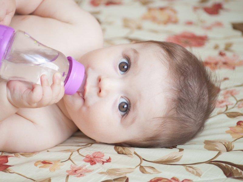 Младенец пьет укропную водичку из бутылочки