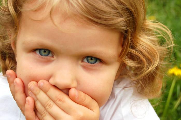 Девочка закрывает рот руками