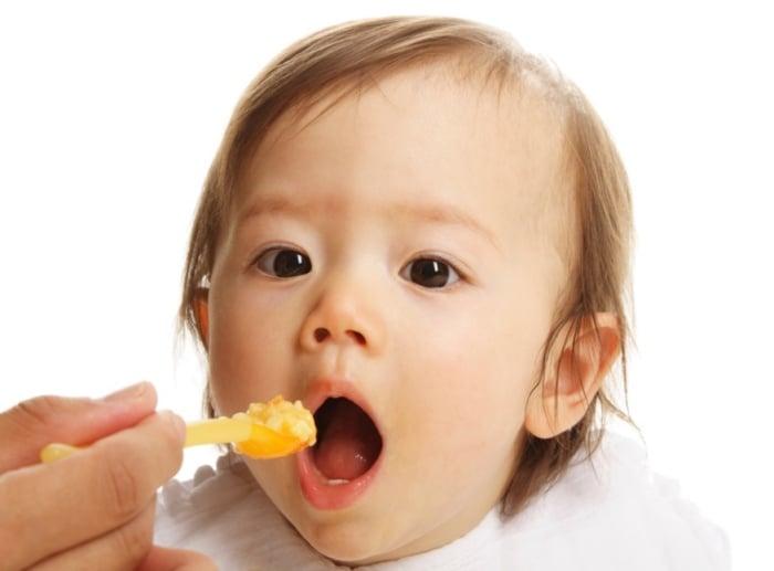 Ребенок открыл рот перед ложкой