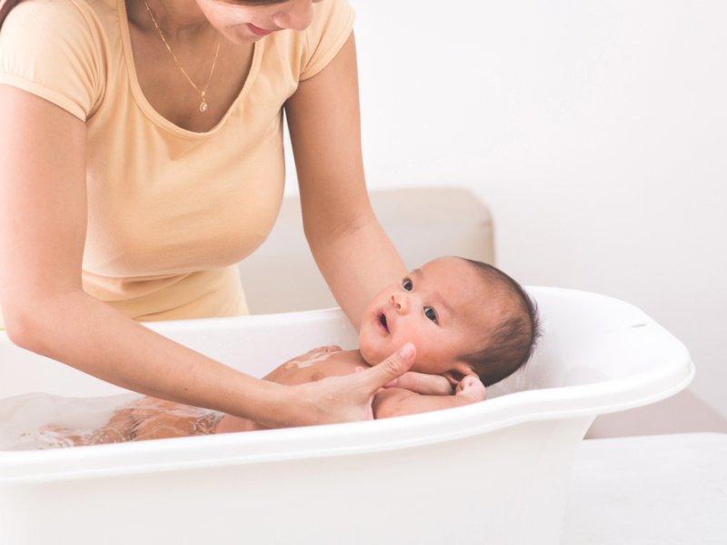 Мама купает новорожденного