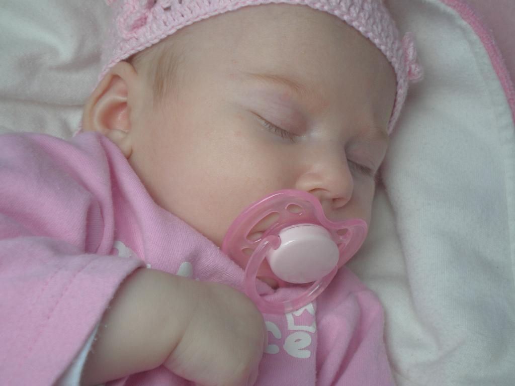 Младенец спит с пустышкой